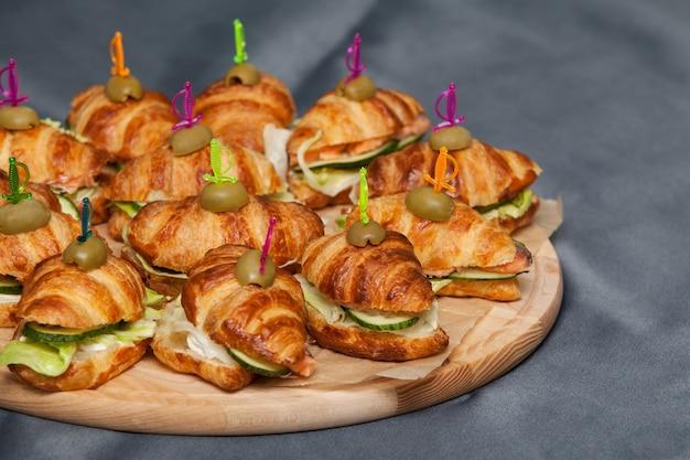 Kanapka croissant z łososiem, sałatą i ogórkami. rogaliki z czerwoną rybą na drewnianej desce do krojenia.