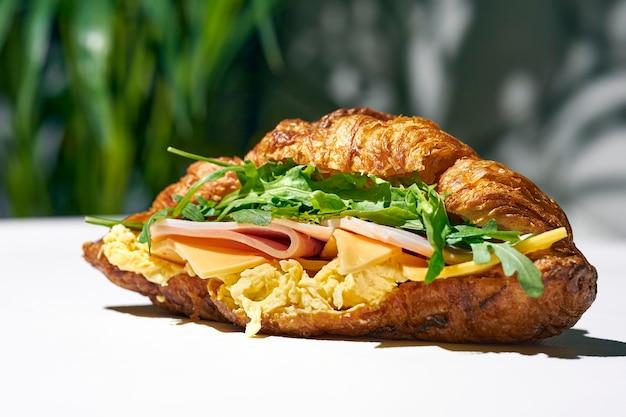 Kanapka croissant z mortadelą, serem, rukolą i jajecznicą. ostre światło. białe tło