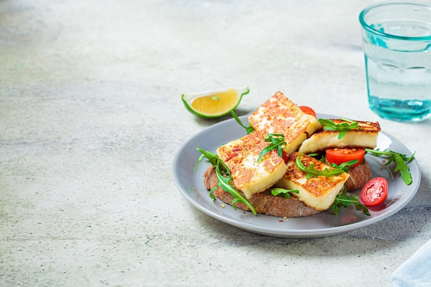 Kanapka halloumi smażona z rukolą i pomidorami na szarym talerzu. tosty z grillowanym serem i pomidorami.