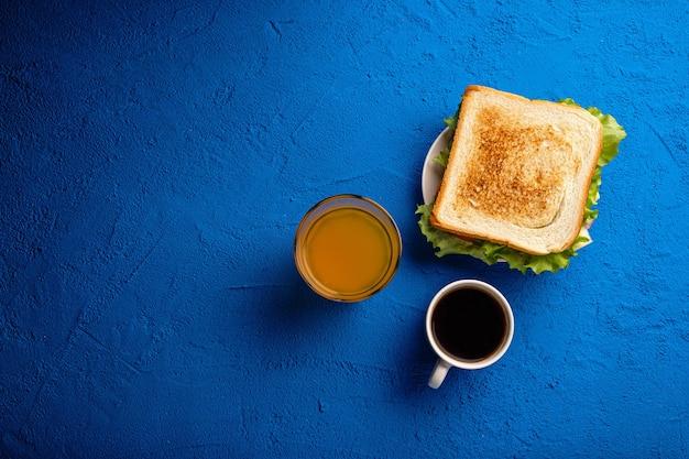Kanapka, kawa i sok na blacie stołu