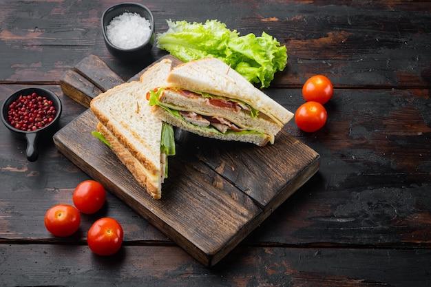 Kanapka klubowa panini z szynką, świeżym pomidorem, serem, na ciemnym tle drewnianych