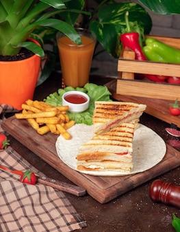 Kanapka klubowa podawana z frytkami i napojem bezalkoholowym, majonezem, keczupem