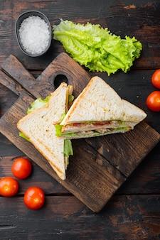 Kanapka klubowa z mięsem, serem, pomidorem, szynką, na starym drewnianym stole, widok z góry