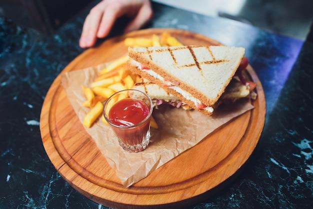 Kanapka klubowa z serem, ogórkiem, pomidorem i wędzonym mięsem. przyozdobionym frytkami.