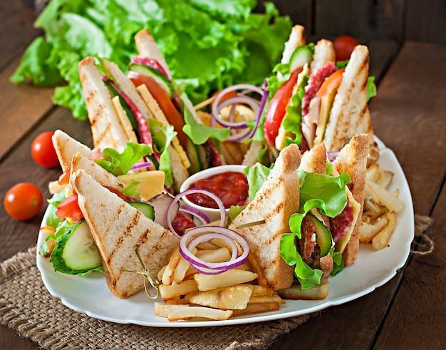Kanapka klubowa z serem, ogórkiem, pomidorem, wędzonym mięsem i salami. podawany z frytkami.