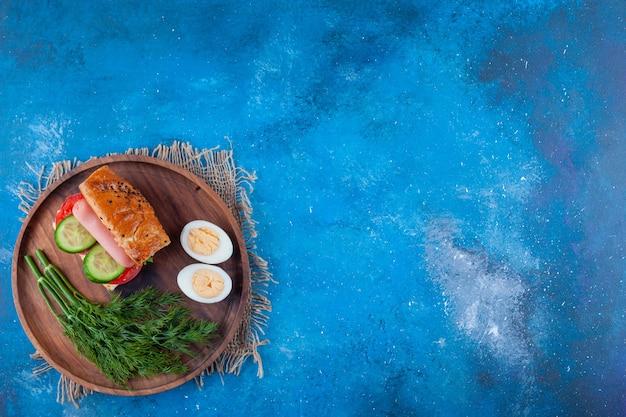 Kanapka, koperek i jajko w plasterkach na pokładzie na niebiesko.