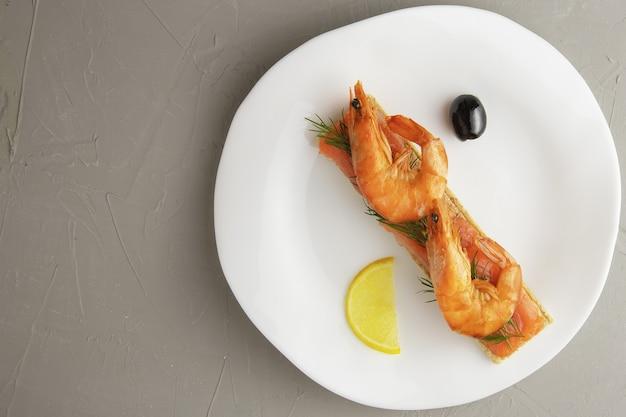 Kanapka lub tost z kawałkami czerwonego pstrąga i krewetkami z gałązką koperku na białym talerzu na betonowej powierzchni