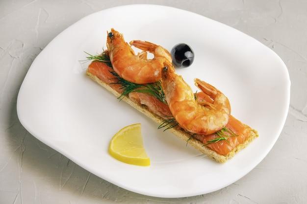 Kanapka lub tost z kawałkami czerwonego pstrąga i krewetkami z gałązką koperku na białym talerzu na betonowym tle lub powierzchni, dietetyczny pokarm dla sprawności, widok z góry, zbliżenie