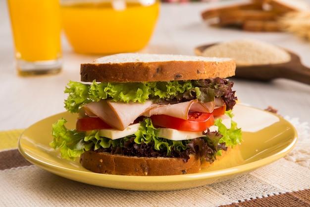 Kanapka na białym talerzu z piersią indyka, pomidorem, sałatą i serem na stole