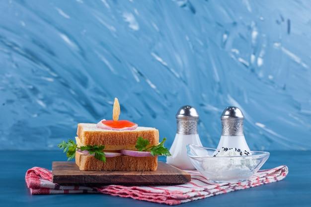 Kanapka na desce obok soli i miska sera na ściereczce, na niebieskim stole.
