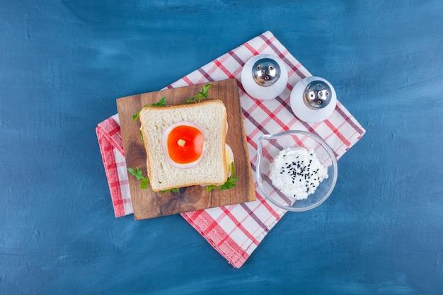 Kanapka na desce obok soli i miska sera na ściereczce, na niebiesko.