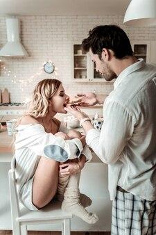 Kanapka na śniadanie. brunetka, brodaty mężczyzna w białej koszuli, czuje się dobrze, gdy daje kanapkę swojej żonie