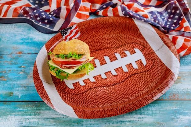 Kanapka na talerzu piłki futbol amerykański z amerykańską flagą