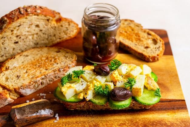 Kanapka otwarta z tradycyjną niemiecką sałatką ziemniaczaną, chlebem, oliwkami na desce do krojenia