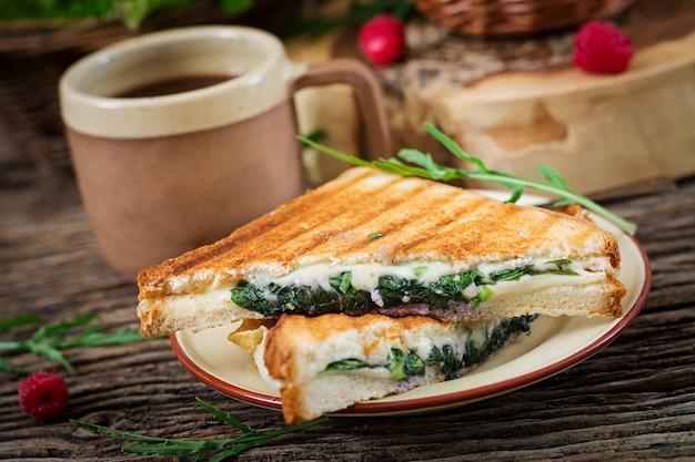Kanapka panini z liśćmi sera i musztardy. poranna kawa. śniadanie na wsi