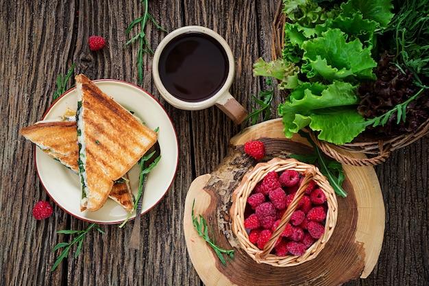 Kanapka panini z liśćmi sera i musztardy. poranna kawa. śniadanie w wiosce