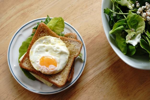 Kanapka pełnoziarnista z jajkami, świeżymi warzywami, szynką i serem, zdrowe śniadanie na nowy dzień, który jest szczęśliwy i zdrowy.