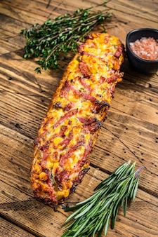 Kanapka pizza na chleb bagietki z szynką, boczkiem, warzywami i serem na drewnianym stole. drewniane tła. widok z góry.