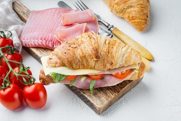 Kanapka rogalik z prosciutto, pomidorami, zestawem sera, ziołami i składnikami, na białym tle kamienia