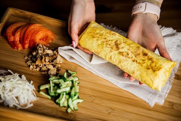Kanapka shawarma t z chleba pita, falafel. tradycyjna przekąska z bliskiego wschodu w ręku na drewnianym stole