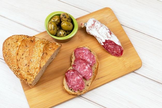 Kanapka suszonych kiełbas, oliwek i bochenka chleba pełnoziarnistego na desce.