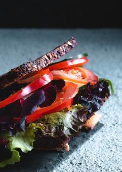 Kanapka warzywna z pomidorem, sałatą, cukinią, ogórkiem i innymi warzywami.