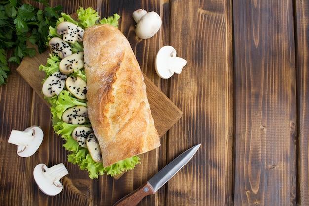 Kanapka wegetariańska z pieczarkami, liśćmi sałaty i czarnym sezamem na desce do krojenia