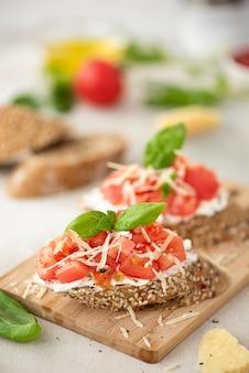 Kanapka wegetariańska z różowymi pomidorami, parmezanem i bazylią