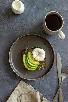 Kanapka z awokado i jajkiem w koszulce. zdrowe jedzenie wegetariańskie. śniadanie.