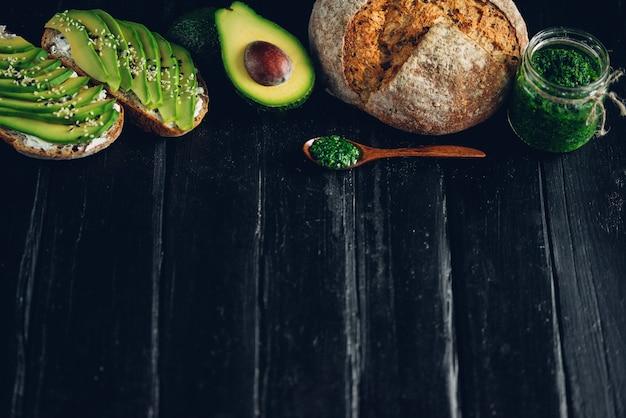 Kanapka z awokado na ciemnym chlebie żytnim ze świeżym pokrojonym z góry awokado. copyspace dla twojego tekstu