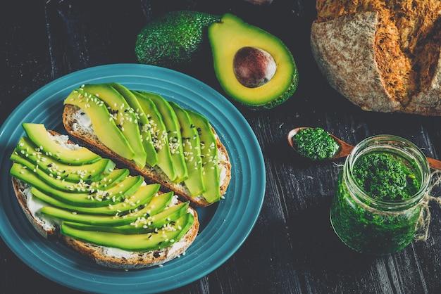 Kanapka z awokado na ciemnym chlebie żytnim ze świeżym pokrojonym z góry awokado.