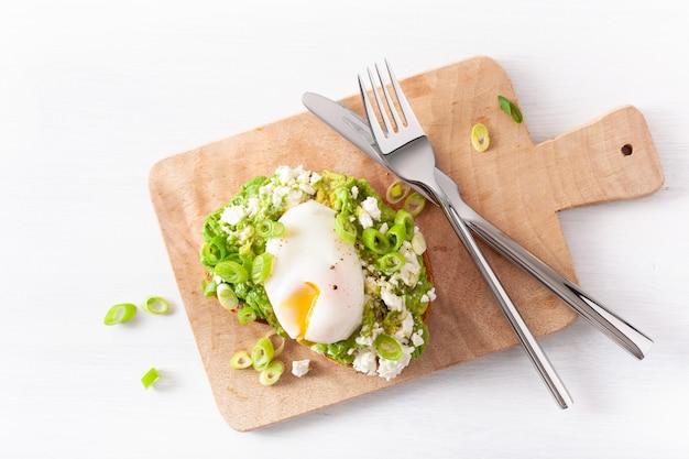 Kanapka z awokado na śniadanie z jajkiem w koszulce i serem feta