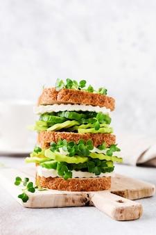 Kanapka z awokado, ogórkiem i serem feta udekorowana mikro-zieleniną i chlebem wieloziarnistym na prostym drewnianym stojaku na zdrowe śniadanie