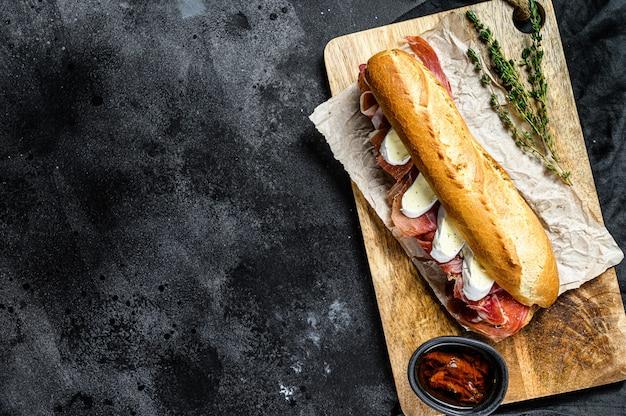 Kanapka z bagietką z szynką jamonową serrano, paleta iberica, ser camembert na desce do krojenia. czarne tło, widok z góry, miejsce na tekst