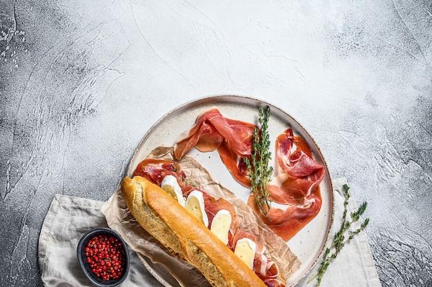 Kanapka z bagietką z szynką jamonową serrano, paleta iberica, ser camembert na desce do krojenia. szara powierzchnia, widok z góry, miejsce na tekst