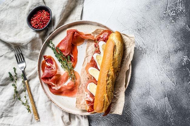 Kanapka z bagietką z szynką prosciutto, serem camembert na talerzu. szare tło, widok z góry.