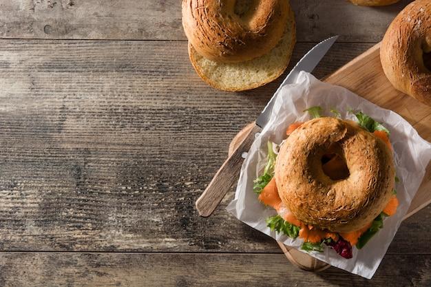 Kanapka z bajgli z twarogiem, wędzonym łososiem i warzywami na drewnianym stole