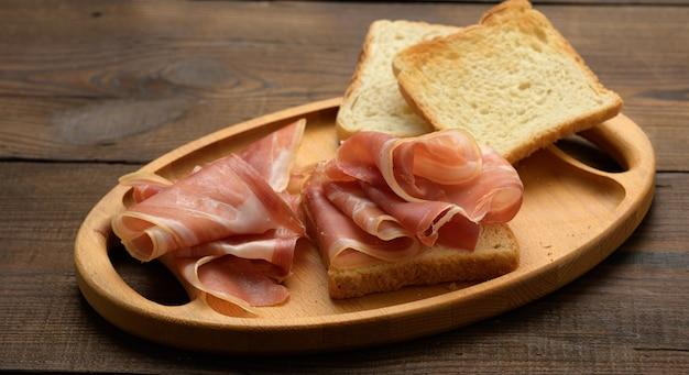 Kanapka z białą kwadratową kromką chleba i kromkami prosciutto na drewnianej desce