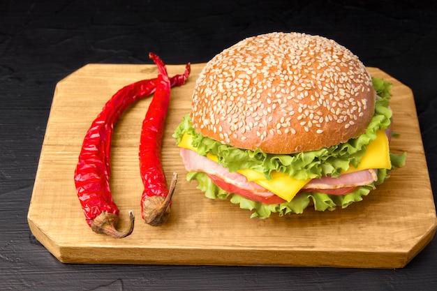 Kanapka z boczkiem i warzywami obok gorącej czerwonej papryki na drewnianej desce