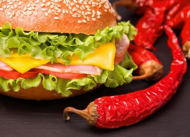 Kanapka z boczkiem i warzywami obok ostrej czerwonej papryki