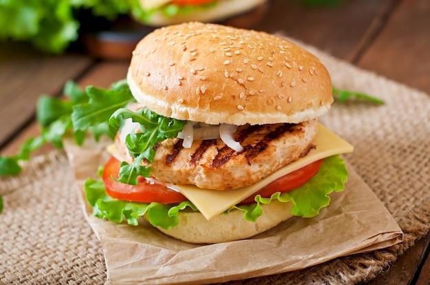 Kanapka z burgerem z kurczaka, pomidorami, serem i sałatą