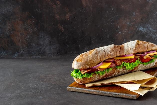 Kanapka z ciemnego chleba z sałatką, boczkiem, pomidorami, serem i cebulą. śniadanie. fast food.