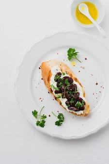 Kanapka z czerwoną fasolą, czosnkiem, oliwą z oliwek i twarogiem na białej powierzchni