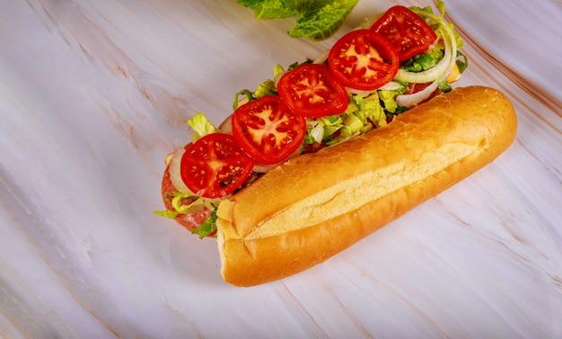 Kanapka z francuskim chlebem, serem muenster, salami i warzywami.