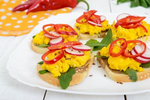 Kanapka z jajecznicą, rukolą, rzodkiewką, papryką kapi i nasionami lnu na talerzu