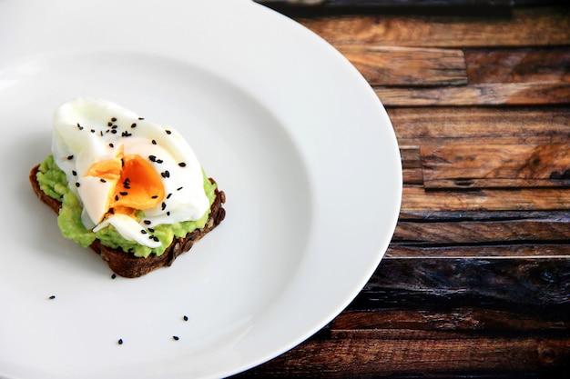 Kanapka z jajkiem w białym talerzu na drewnianym tle