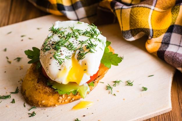 Kanapka z jajkiem w koszulce i pomidorem na desce do krojenia