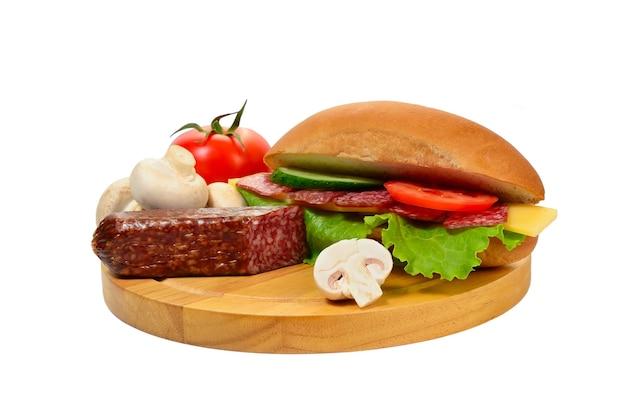 Kanapka z kiełbasą i warzywami na deska do krojenia na białym tle