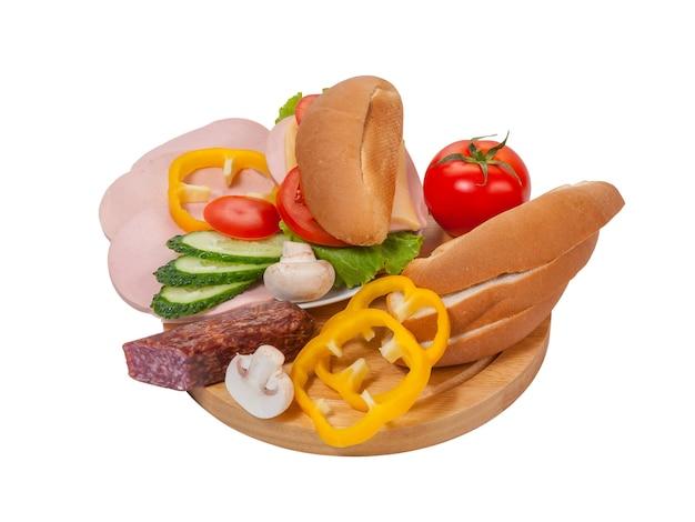 Kanapka z kiełbasą i warzywami na talerzu, chleb i warzywa na deska do krojenia na białym tle