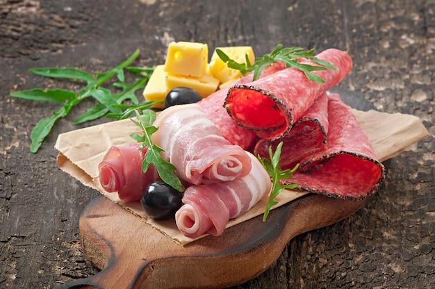 Kanapka z kiełbasą, oliwką, pomidorem i rukolą na starym drewnianym